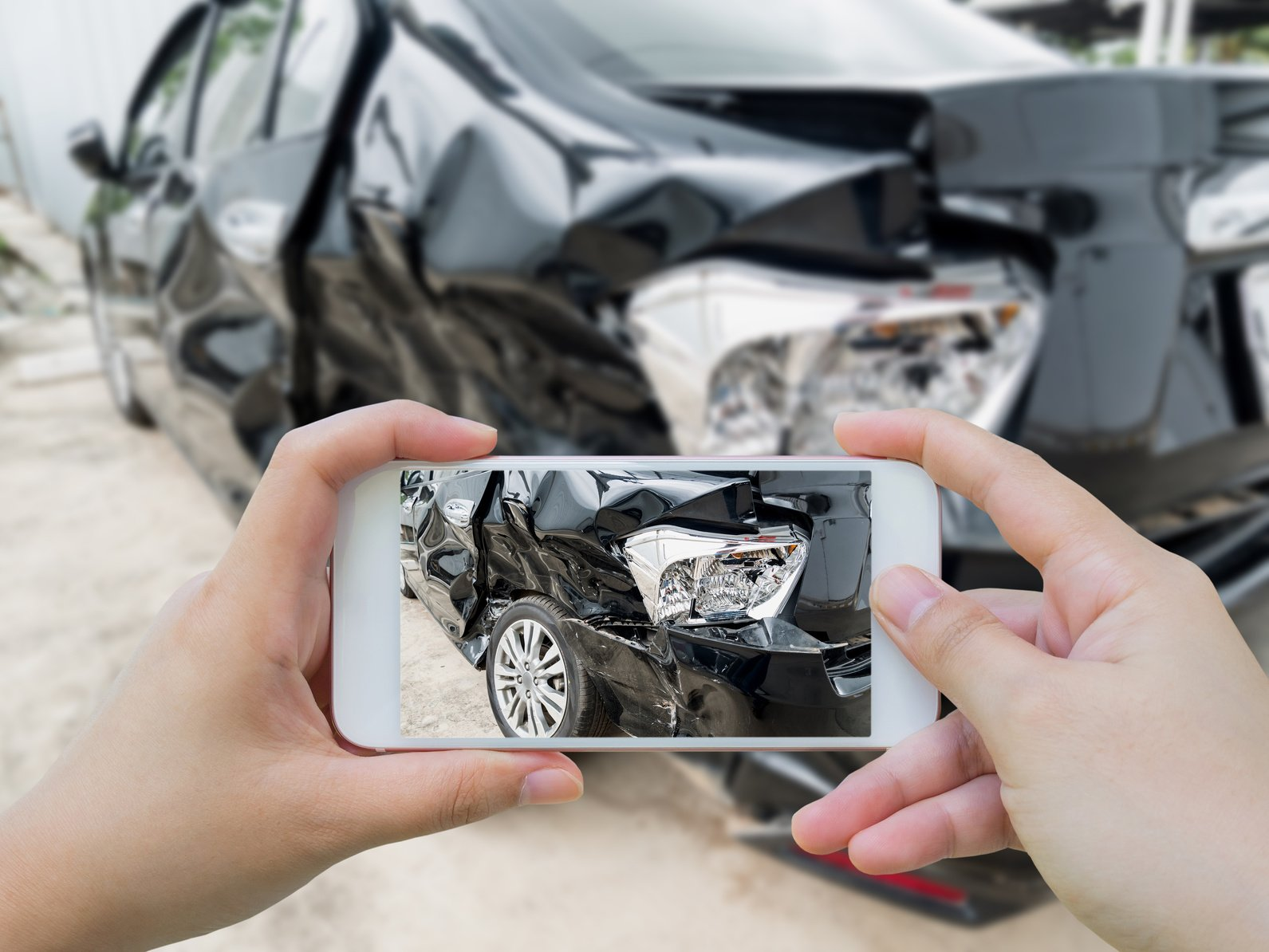 Car crash accident damaged with hand using smartphone taking photo before contacting a dedicated Sheffield Village auto accidents lawyer